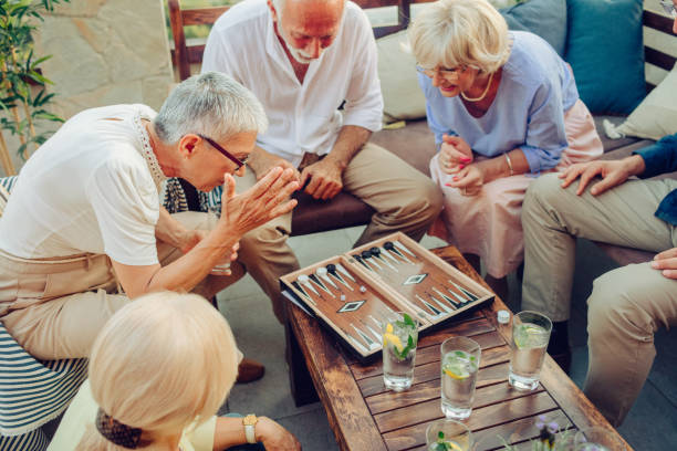 senior friends playing backgammon - backgammon stock pictures, royalty-free photos & images