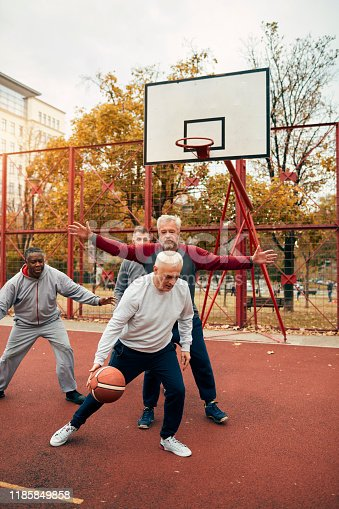Four senior friends playing basketball outdoors.