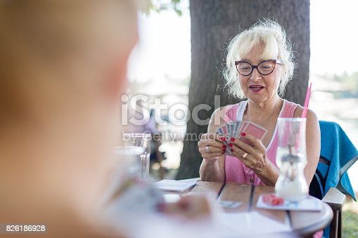 istock Senior friends playing cards 826186928