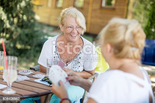 istock Senior friends playing cards 828408862
