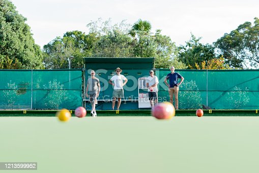 Four senior male friends playing social lawn bowls outdoors