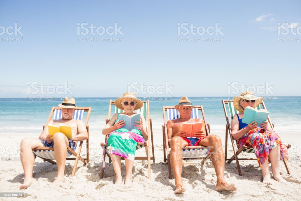Senior friends reading books on beach chair stock photo