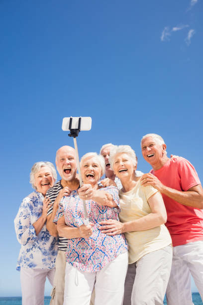senior freunde nehmen selfie - senior bilder wasser stock-fotos und bilder