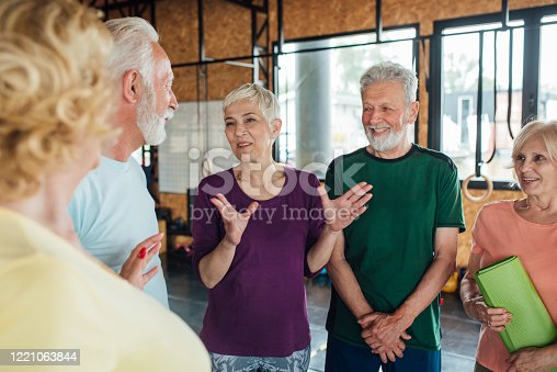 1047537292 istock photo Senior friends talking and having fun before their group yoga class 1221063844
