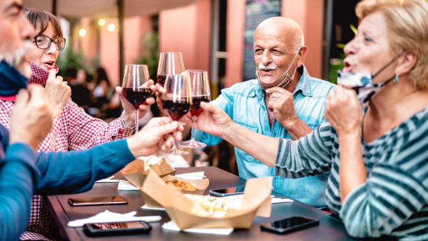 Senior friends toasting wine at restaurant bar wearing opened face mask - New normal lifestyle concept with happy mature people having fun together at garden party - Warm filter with focus on bald man stock photo