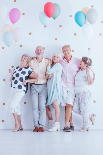 senioren freunde mit bunten luftballons - rentenpunkte stock-fotos und bilder