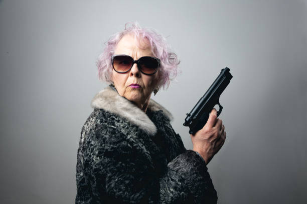 senior gangster lady holding gun Senior woman, wearing fur coat and sunglasses, holding gun in her hand,  she has pink curly hair gangster stock pictures, royalty-free photos & images