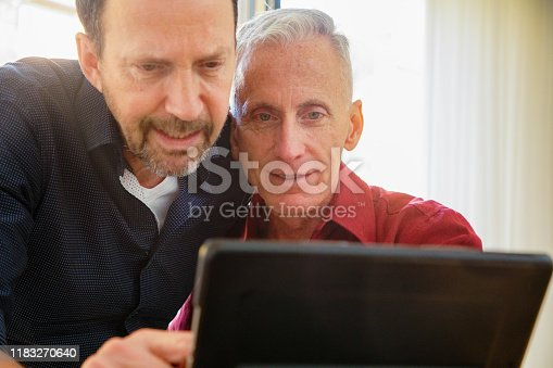 Senior gay couple looking closely at news on tablet