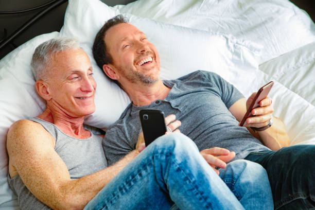 senior gay couple sharing mobile phone media in bed on a weekend afternoon - telemóvel ao lado da cama imagens e fotografias de stock