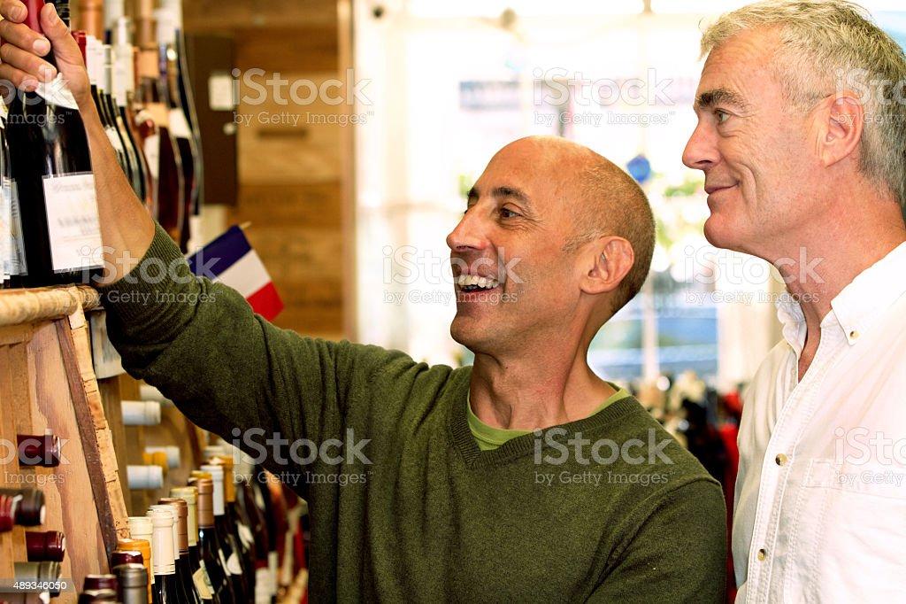 Senior Gay Male Couple Buying French Wine to Celebrate stock photo