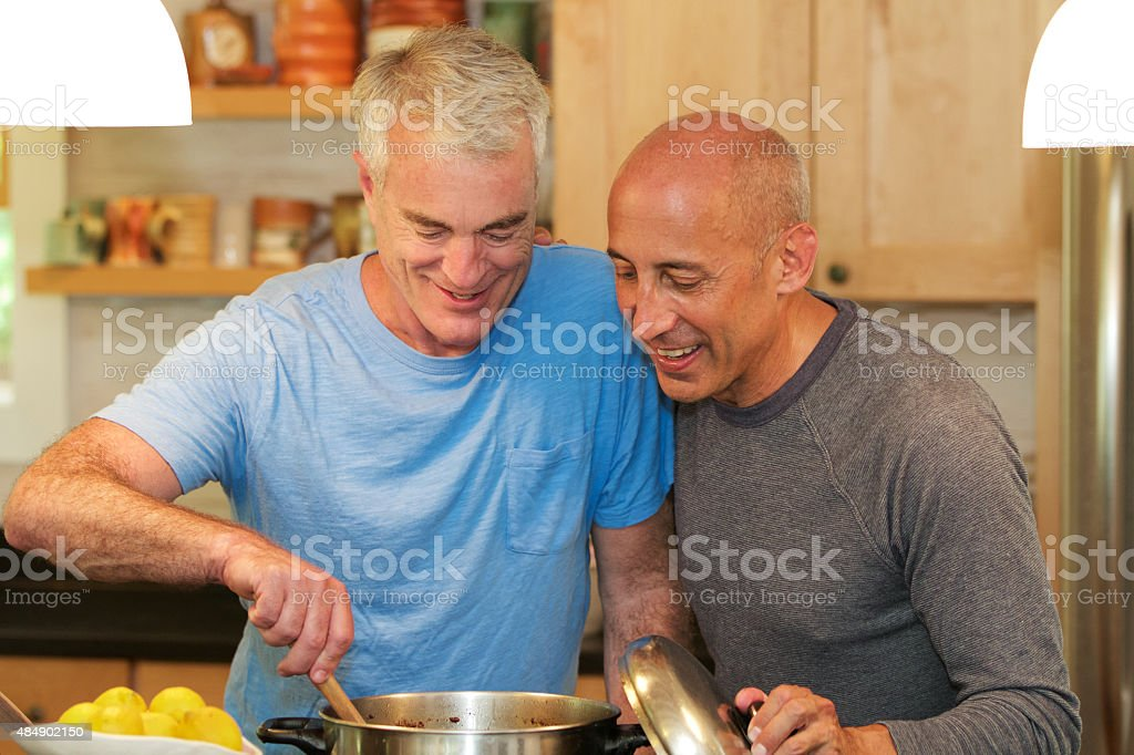 Senior Gay Male Couple Cooking and Smiling in Kitchen stock photo