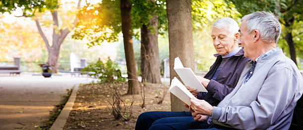 Senior gay male couple enjoying reading books in park panorama stock photo