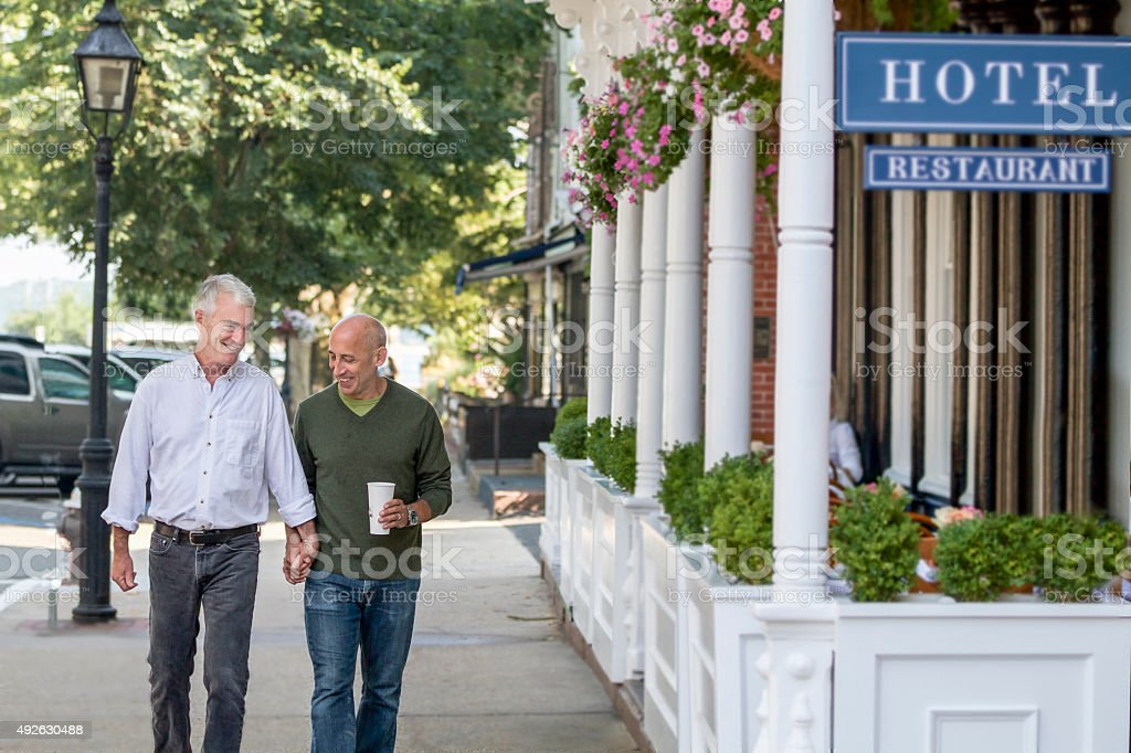 Senior Gay Male Couple Holding Hands on Village Main Street stock photo