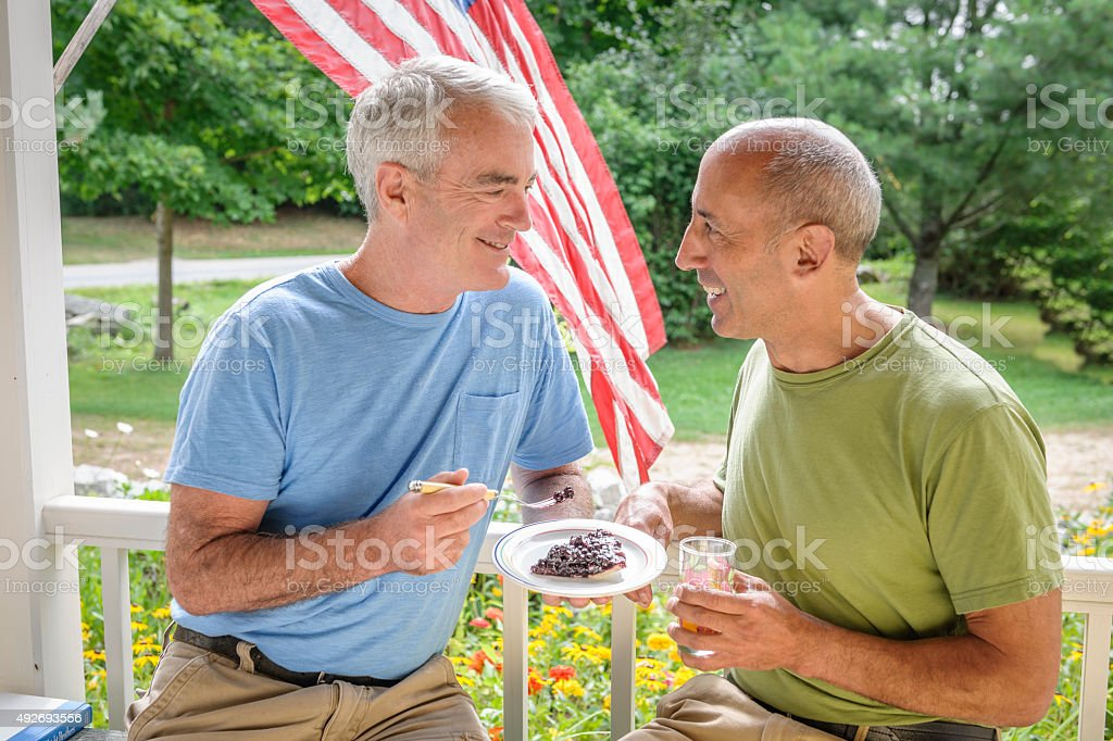 Senior Gay Male Couple on Porch of Bed and Breakfast stock photo