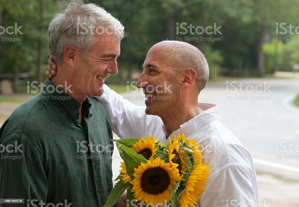 Senior Gay Male Couple with Sunflowers Bouquet on Country Road stock photo