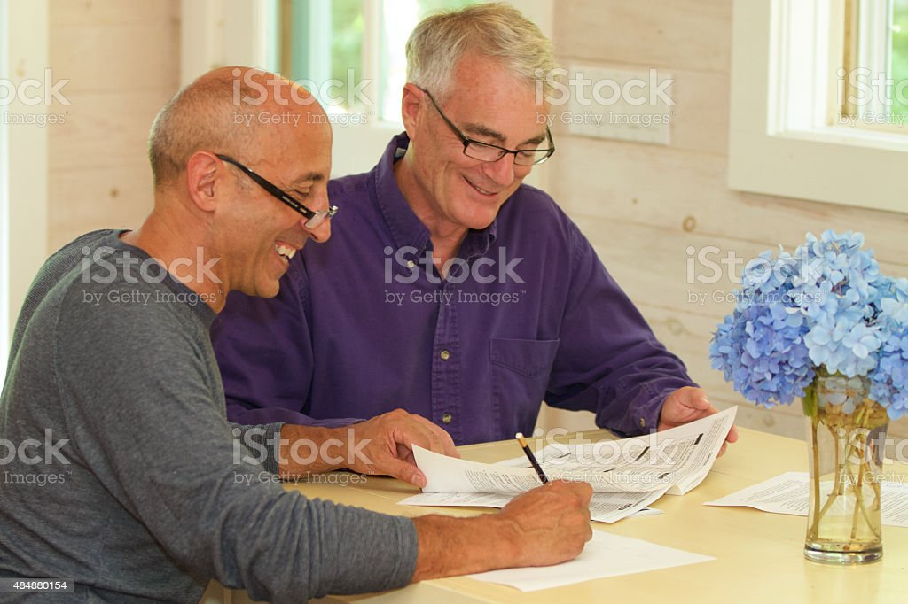 Senior Gay Male Couple Working Together on Financial Documents Senior gay male couple, smiling and affectionate, working at their kitchen table on financial documents such as wills, financial planning, or a contract for a house. 2015 Stock Photo