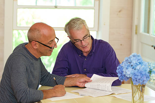 Senior Gay Male Couple Working Together on Financial Documents Older, mature, senior gay male couple, affectionate and in love, working together on financial documents at their dining room table at home. gay couple stock pictures, royalty-free photos & images