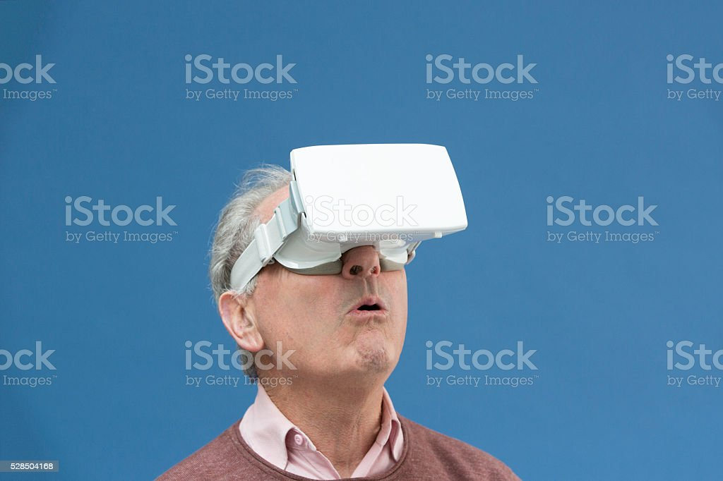 Senior gentleman is surprised while using a virtual reality headset stock photo