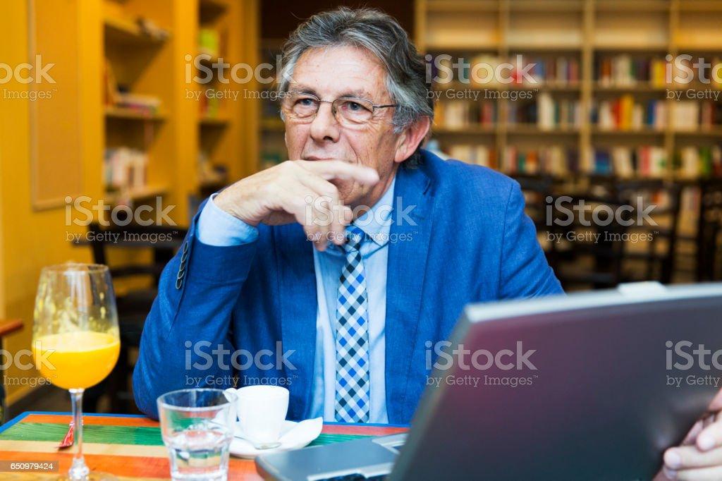 Senior gentleman sitting in a library,drinking orange juice stock photo