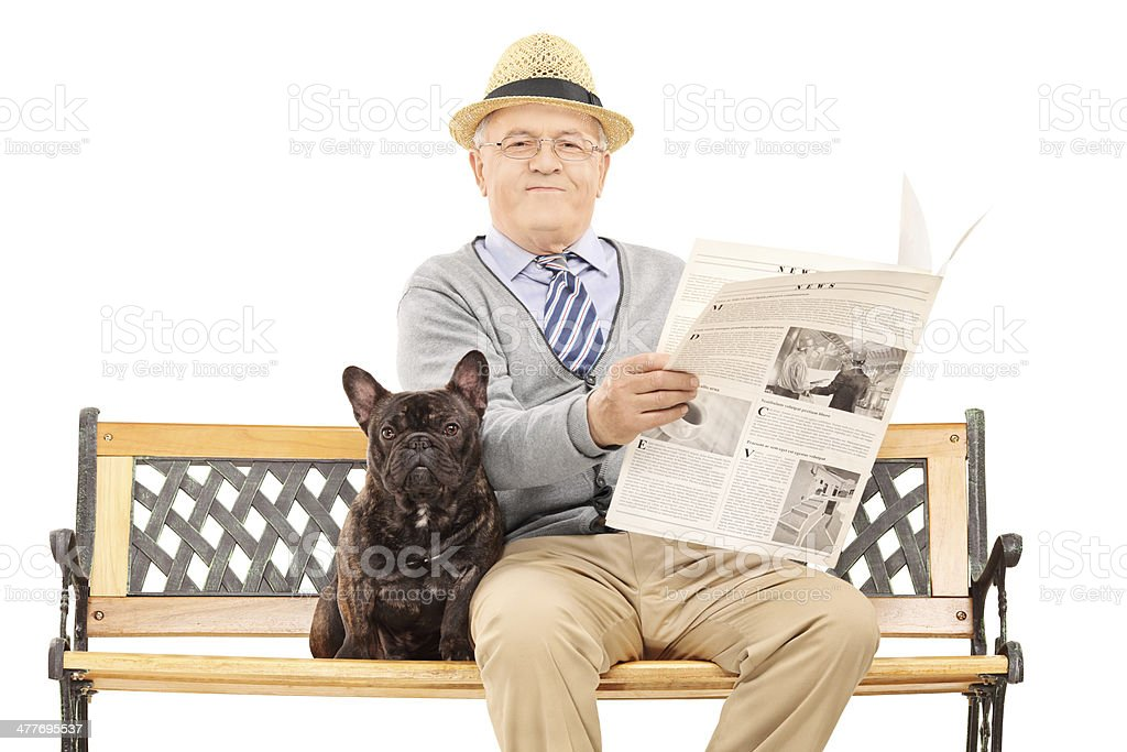 Senior gentleman sitting with his dog and reading newspaper royalty-free stock photo