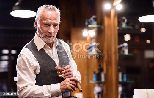 istock Senior gentleman with glass and cigar 623691426