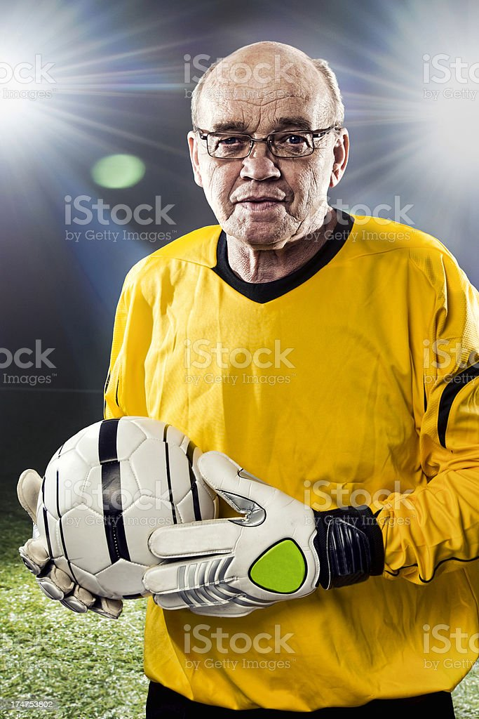 Senior goalkeeper is holding a ball at soccer stadium royalty-free stock photo