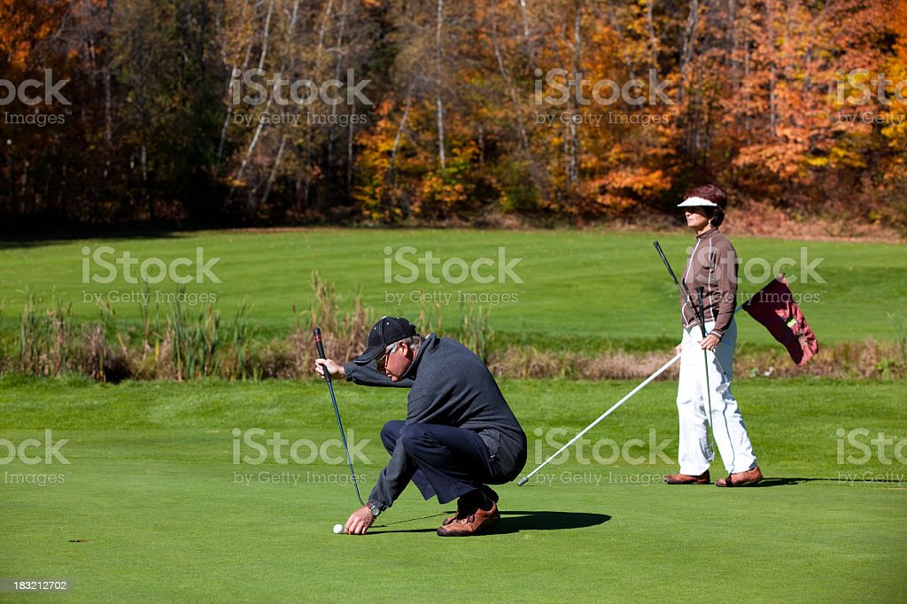 Senior Golf Players Couple in Action on Putting Green royalty-free stock photo