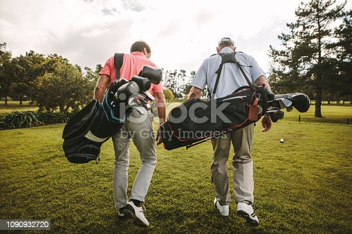 Rear view of two senior golf players walking together in the golf course with their golf bags. Senior golfers walking out of the course after the game.