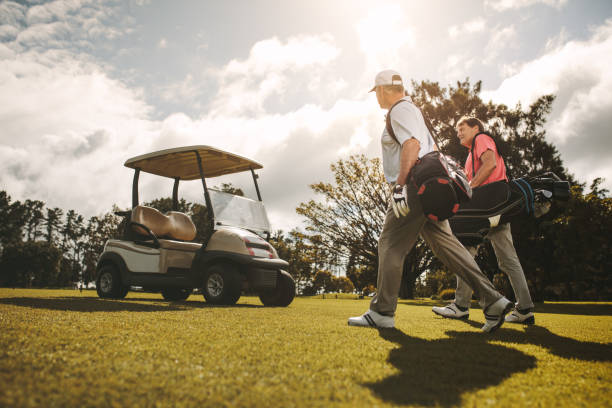 Senior golfer after a game on the court Senior golfers walking together in the golf course with their golf bags. Senior golfers walking and talking after the game. golf cart stock pictures, royalty-free photos & images