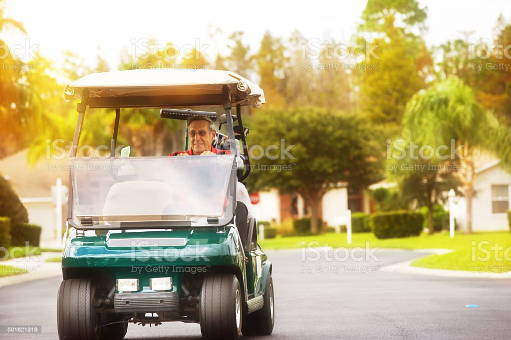 Senior golfer driving golf cart on golf community road stock photo