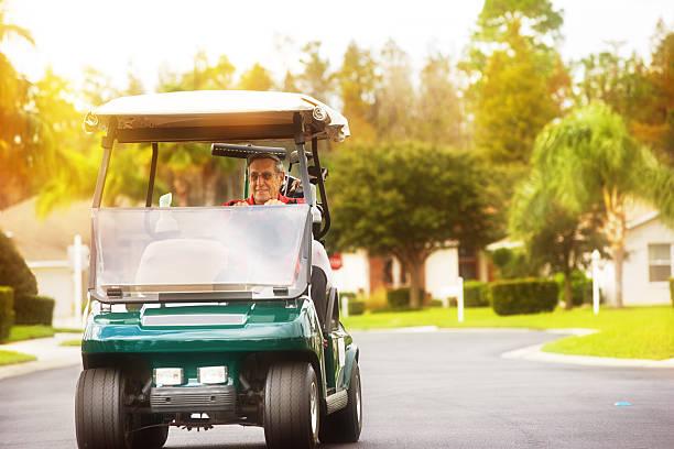 Senior golfeur voiturette conduite sur la route de golf community - Photo