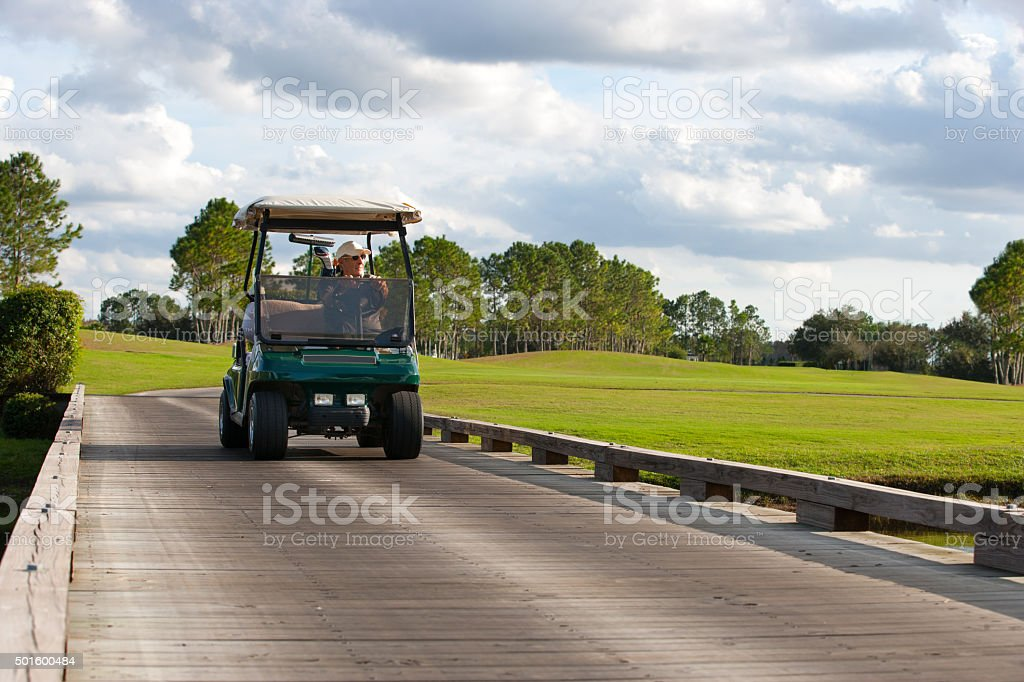 Senior golfer driving golf cart over water hazard stock photo