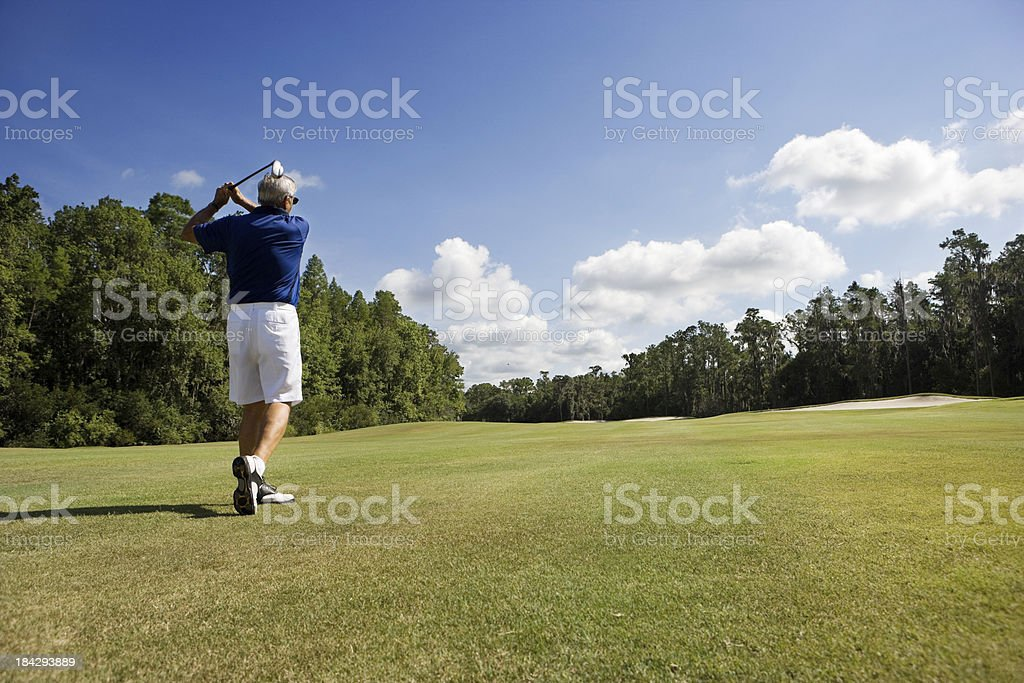 senior golfer on fairway stock photo