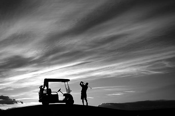 Senior Golfer Swinging by His Golf Cart in Monochrome stock photo