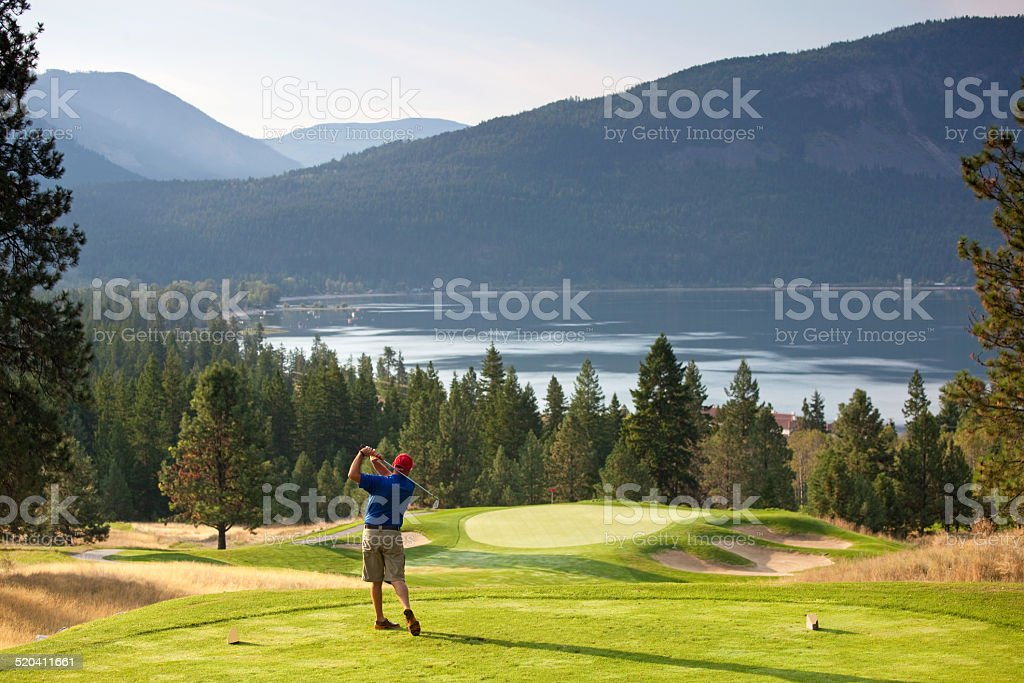 Senior Golfer Swinging on Mountain Golf Course stock photo