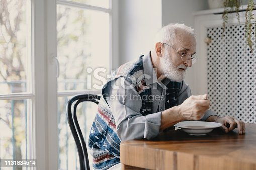 istock Senior grandfather with grey hair and beard sitting alone in the kitchen eating breakfast 1131834514
