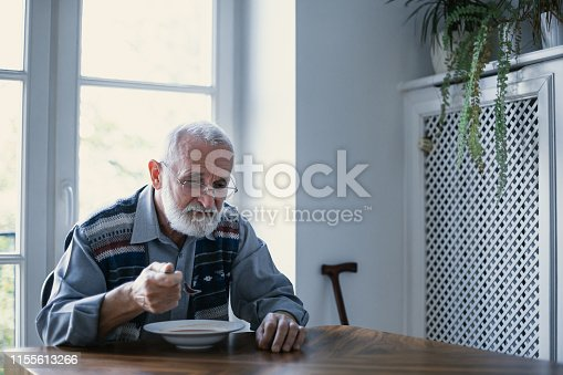 istock Senior grandfather with grey hair and beard sitting alone in the kitchen eating breakfast 1155613266