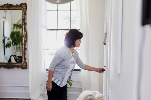 senior grootmoeder anticileert op bezoek; controleert de voordeur - raam bezoek stockfoto's en -beelden