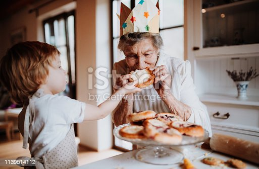 istock Senior grandmother with small toddler boy making and eating cakes at home. 1139514112