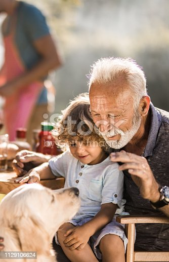 Mature man and his small grandchild enjoying on a picnic lunch with their dog.