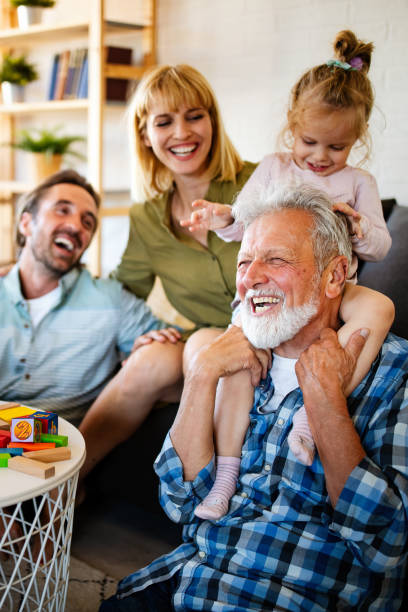 Senior grandparents playing with grandchildren and having fun with family stock photo