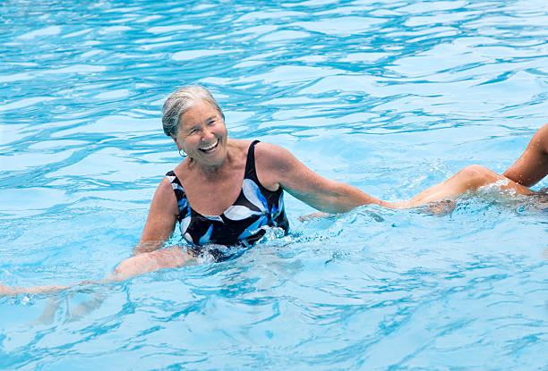 senior graues haar frau sie wasser-aerobic im swimmingpool. - granny legs stock-fotos und bilder