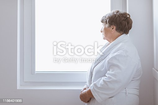istock Senior grey lady wearing white bathrobe standing by the window at nursing home 1156401935