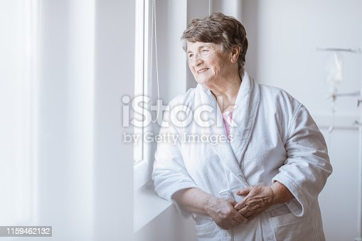 istock Senior grey lady wearing white bathrobe standing by the window at nursing home 1159462132