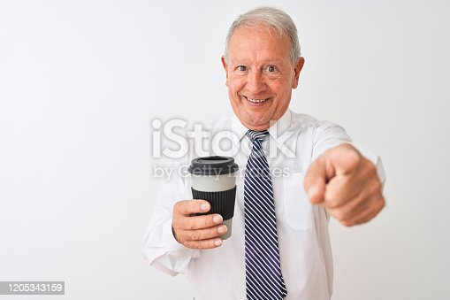 Senior grey-haired businessman drinking take away coffee over isolated white background pointing with finger to the camera and to you, hand sign, positive and confident gesture from the front