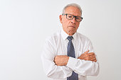 istock Senior grey-haired businessman wearing tie and glasses over isolated white background skeptic and nervous, disapproving expression on face with crossed arms. Negative person. 1205343284