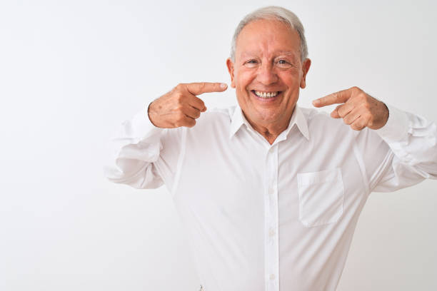 Senior grey-haired man wearing elegant shirt standing over isolated white background smiling cheerful showing and pointing with fingers teeth and mouth. Dental health concept. stock photo
