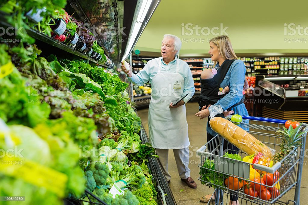 Senior grocery store employee assisting customer in produce section stock photo