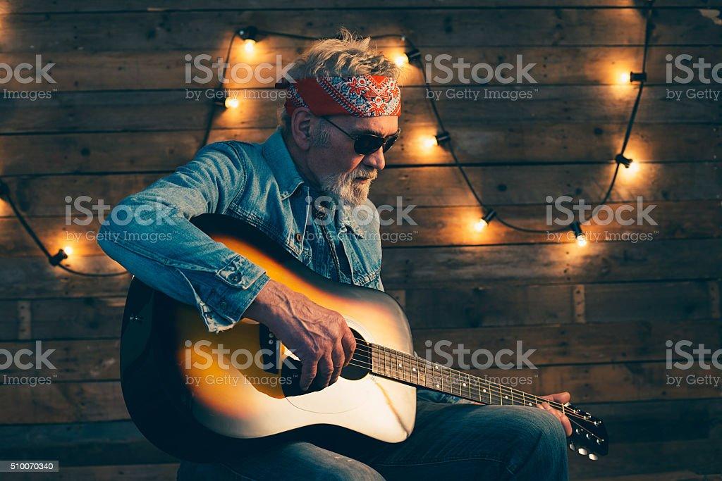 Senior guitarist with beard sitting on chair playing guitar. stock photo