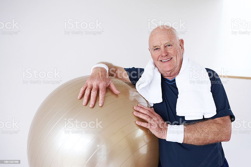 Senior guy with a Pilates ball at the gym royalty-free stock photo
